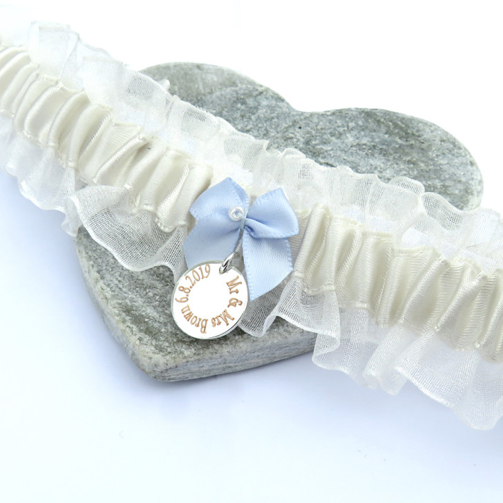 Personalised Something Blue Bow Wedding Garter handmade in the UK from a pale ivory luxury satin ribbon & organza with engraved charm.