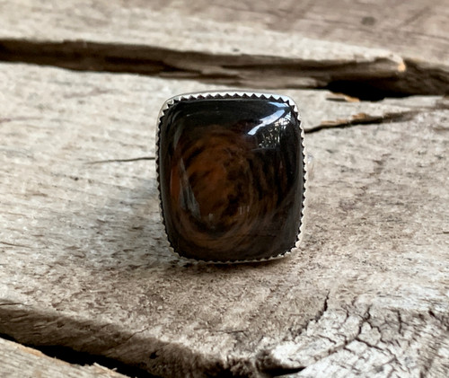 Luminescent Swirly Brown Cushion Cut Rectangle Tiger Eye in a Serrated Setting