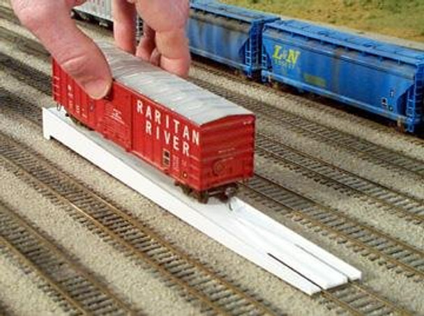 Rix Rail-it on an HO scale train track with a freight car being positioned onto it
