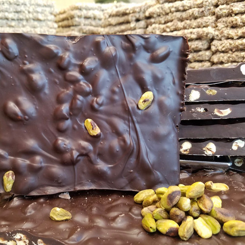 stacks of extra dark chocolate slabs with pistachios throughout and whole pistachios on top