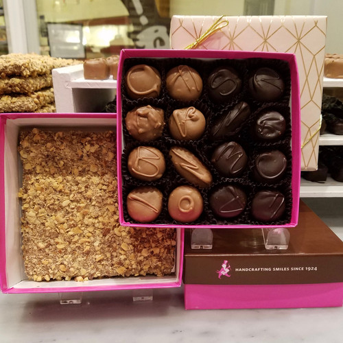 Milk chocolate and dark chocolate covered buttercreams in the top layer of a box with a square of almond covered english toffee on the bottom layer