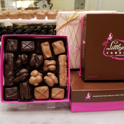 Assortment of milk and dark chocolate covered pecan toffee, caramels, nougat, and nut clusters in a gift box