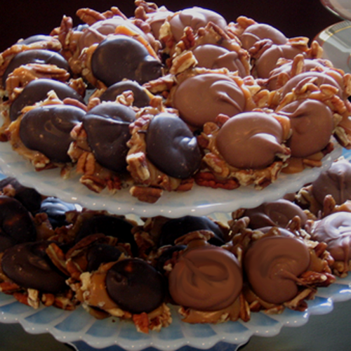 Tiered display tray with milk chocolate and dark chocolate topped pecan and caramel clusters