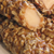 Logs of walnut-covered caramel cut in half to expose a vanilla cream center