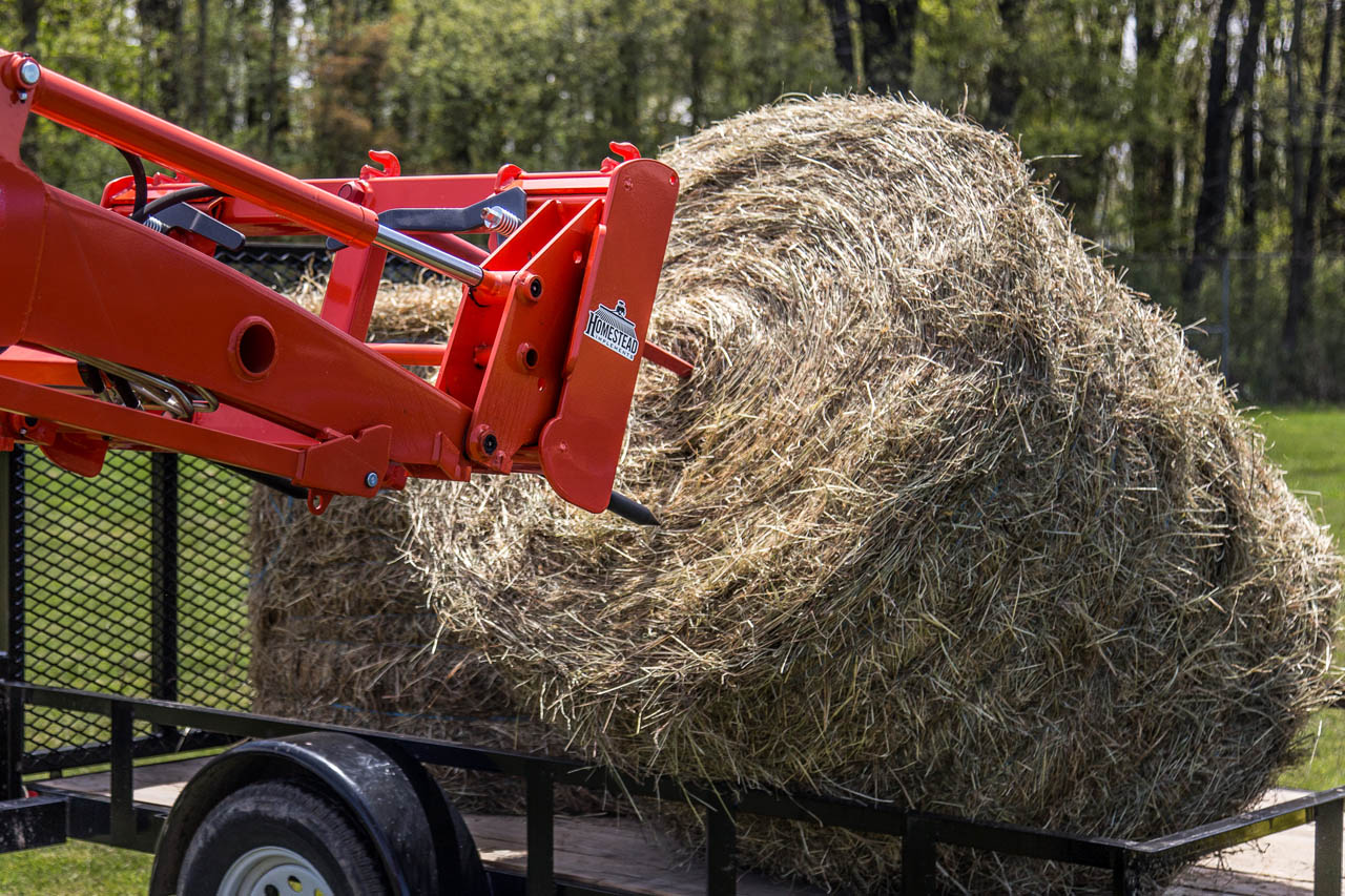 Front-End Independence Bale Spear picking up round bale from trailer.