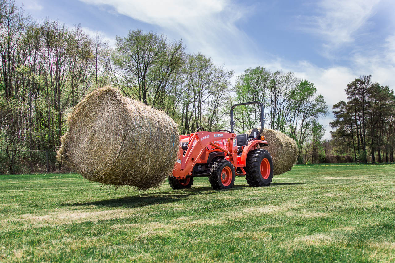Compact Tractor with Round Bale on front and rear spears.