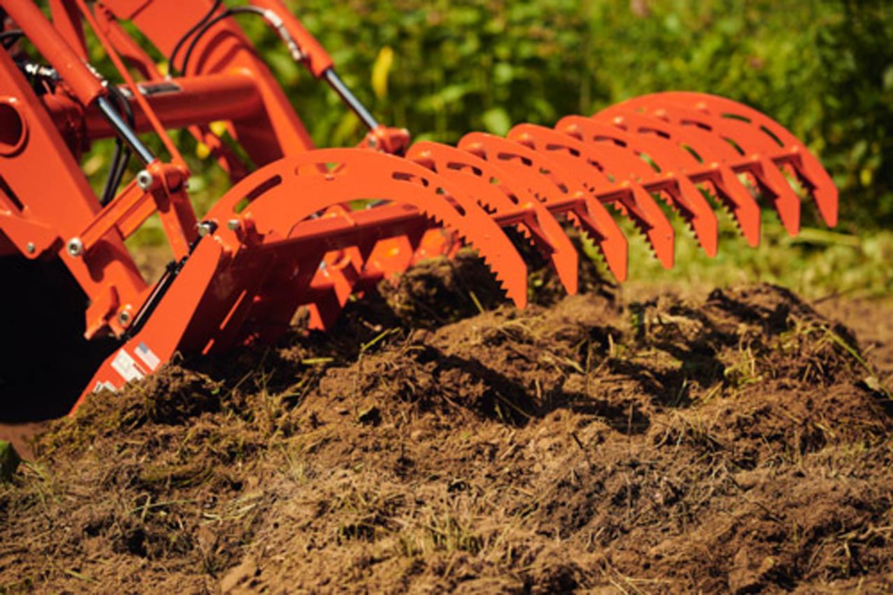 Root Grapple digging in dirt.