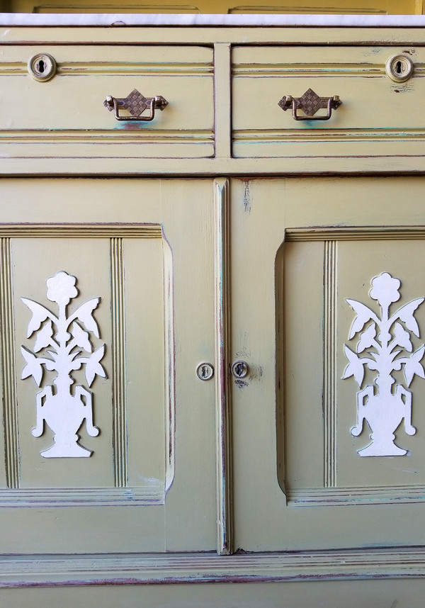 Off-white floral ornamentation on front cabinet doors of Eastlake server.
