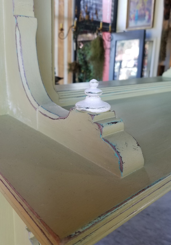 Off-white finial detail and scrollwork on upper shelf of Eastlake hutch.