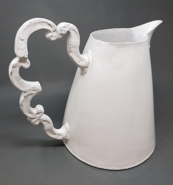 Decorative curlicue-shaped handle on Astier de Villatte pitcher.