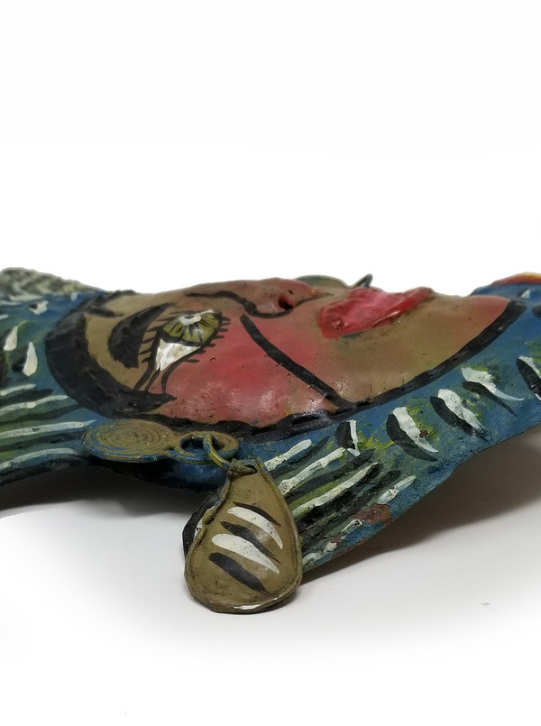 Profile of Mexican fish mask with chased relief in copper.