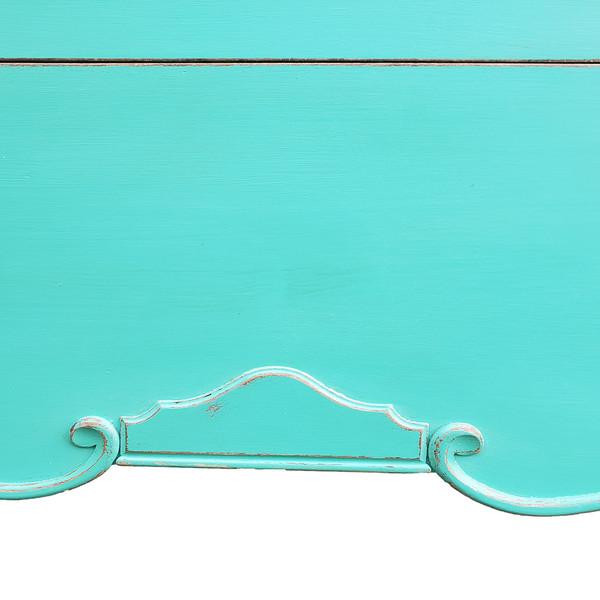 Scrollwork on skirt of painted aqua dresser.