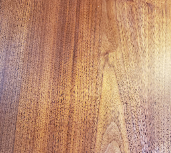 Wood grain surface of vintage walnut dresser.