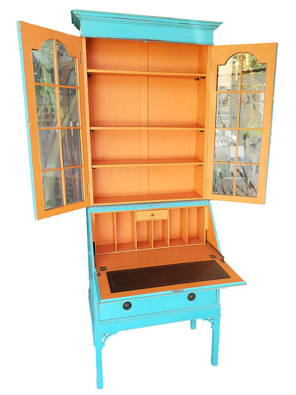 Turquoise and orange secretary with desk and cupboards opened.