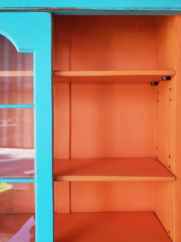 Upper cupboard of secretary desk with bright orange shelves and one glass door open.