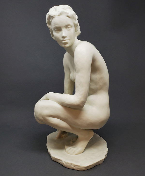German figurative sculpture of squatting woman.