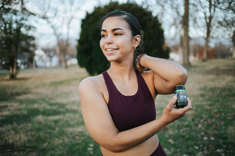 An athlete applies Cornbread hemp's USDA organic CBD balm to her elbow