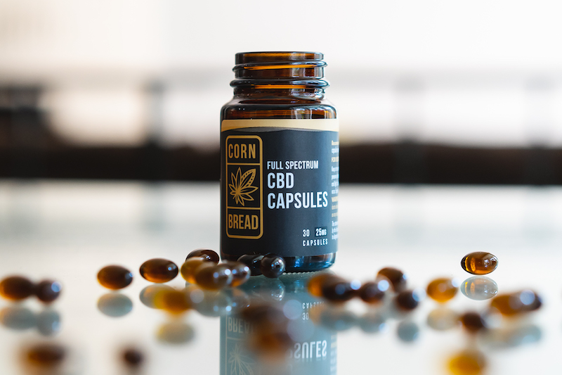 A bottle of Cornbread Hemp USDA organic CBD capsules, with individual capsules shown in the foreground