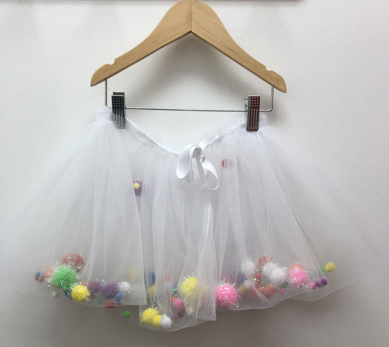 Fun confection! Gathered waist that may be expanded or cinched. Suggested ages 1-4yrs. Tulle and sparkle pom-pom.