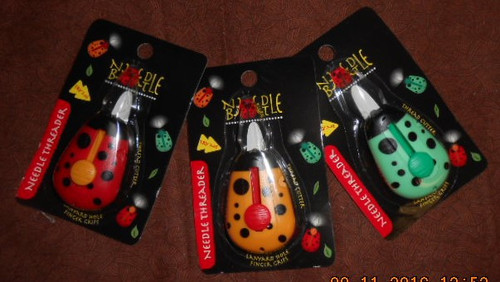 A view of the NeedleBeetle Needle Threaders in their packaging (various colors)