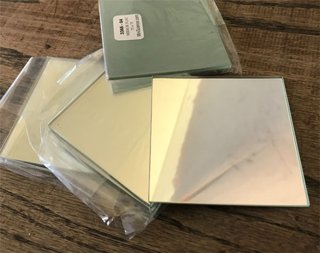 Flat glass mirrors are individually covered by a polybag