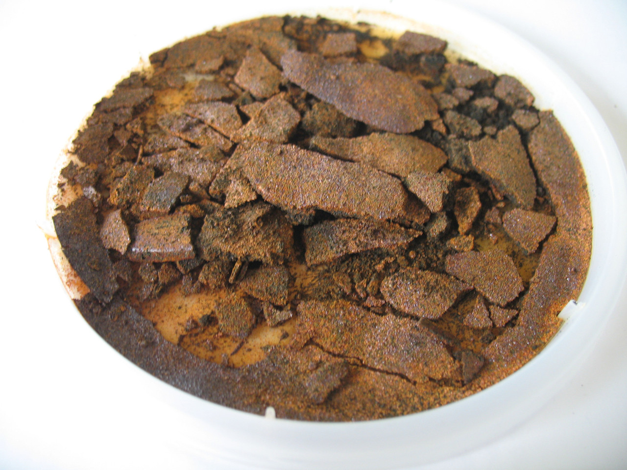 Black iron powder does not rust due to the protective coating. If you intend to make it rust you may spray it with water with added surfactant  or liquid detergent. This image shows rusted S145C.
