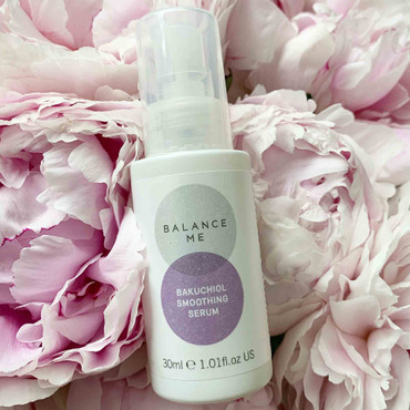 Balance Me Bakuchiol Soothing Serum lying in a bed of flowers