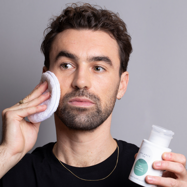 Natural model applying Balance Me BHA Exfoliating Concentrate to his face