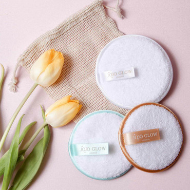 JoJo Glow Cleansing Pads scattered on a pink surface, next to some flowers
