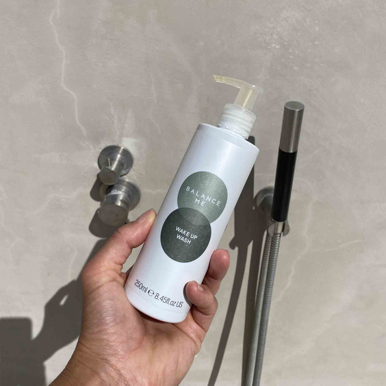 Balance Me Wake Up Wash 250ml being held to camera above a shower