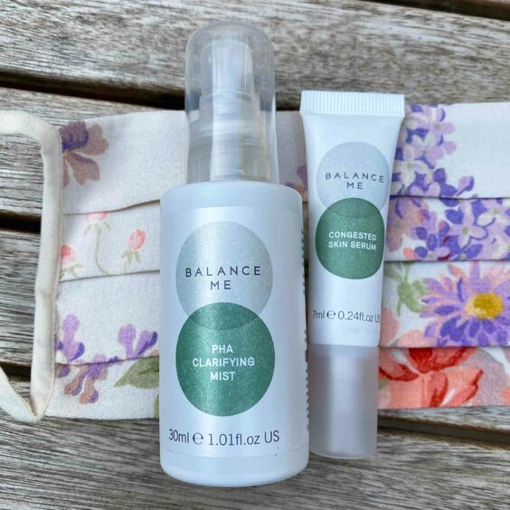Balance Me Congested Skin Serum full size (15ml) and travel size (7ml) lying on a floral pattern