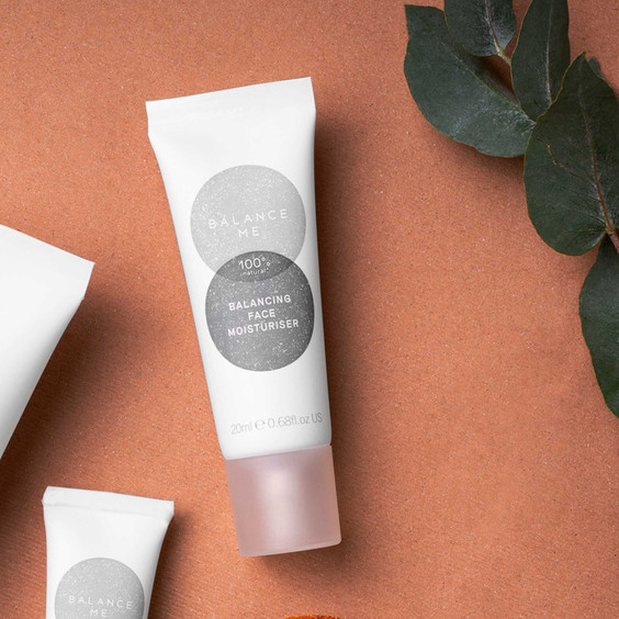 Close up of Balance Me Balancing Face Moisturiser 20ml on a terracotta surface surrounded by other Balance Me products