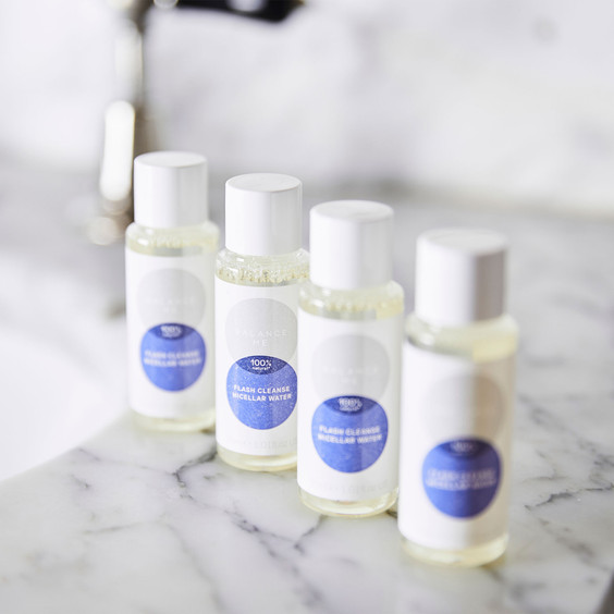 Bottles of Balance Me Flash Cleanse Micellar Water lined up on a marble bathroom surface