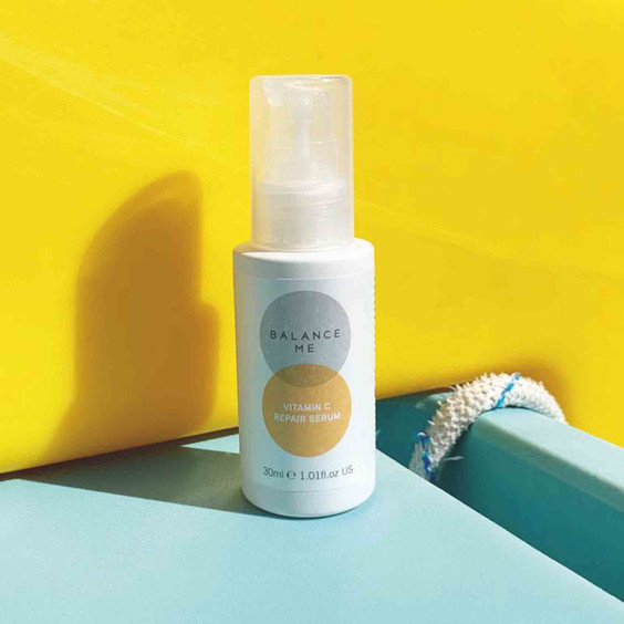 Balance Me Vitamin C Repair Serum against a bright yellow background, casting a long shadow