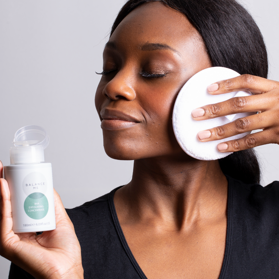 Natural model applying Balance Me BHA Exfoliating Concentrate to her face