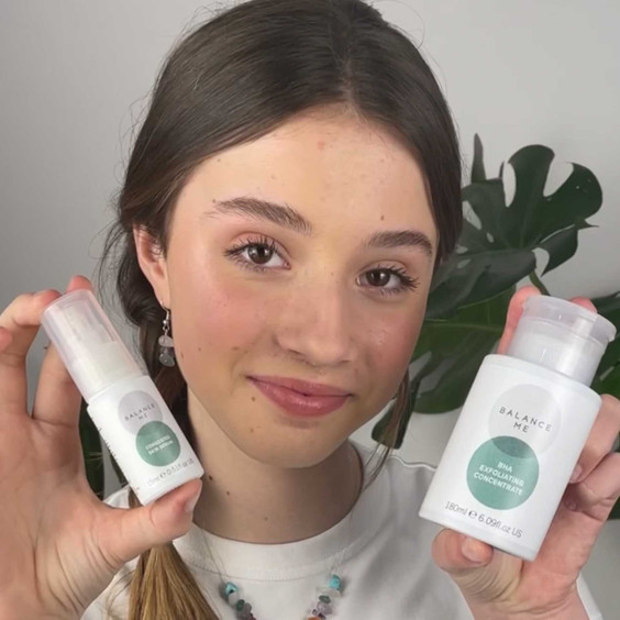 Natural teen model holding Balance Me Clears Pores + Calms bundle (2 products) to camera