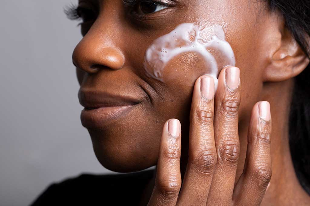 Book a free skincare consultation - image shows our natural model trying a Balance Me skincare product on her cleansed skin.