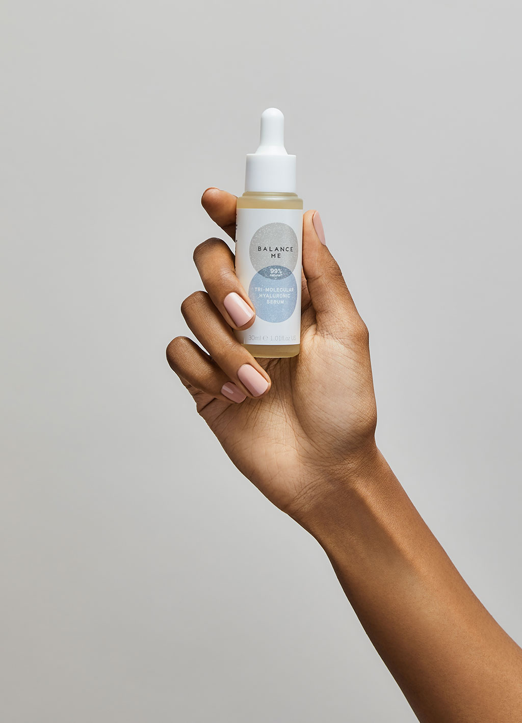 A closeup of the texture of our Balance Me Tri-Molecular Hyaluronic Serum bottle being held