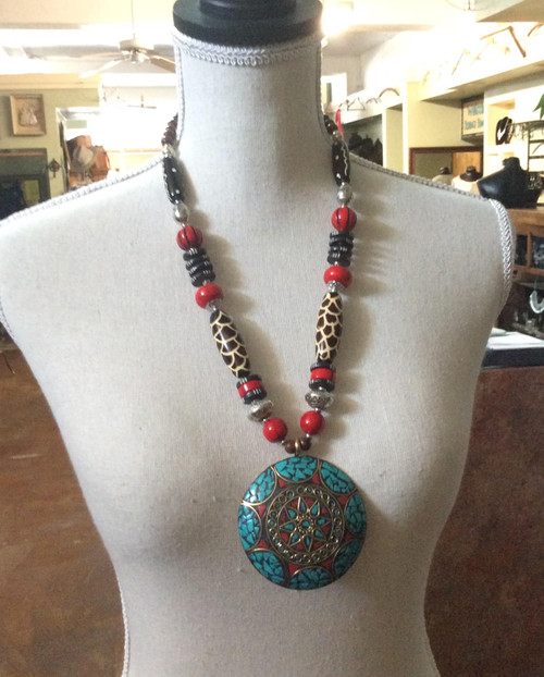Brass and silver bead necklace with round turquoise pendant. Beads are silver, red/black, and animal print at Bijou's Boutique