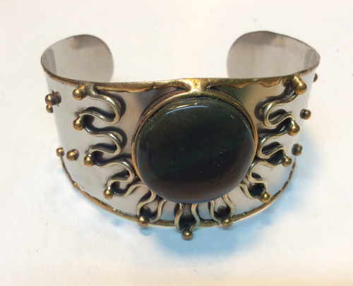 Cuff bracelet with silver metal, brass detail, black and dark green stone at Bijou's Boutique.