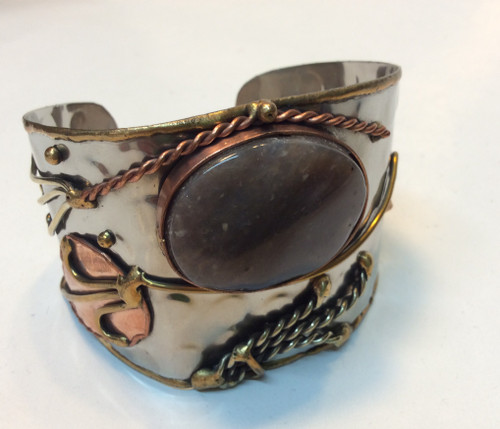 Cuff bracelet with silver hammer metal, brass detail, copper detail, with taupe/purple stone at Bijou's Boutique.