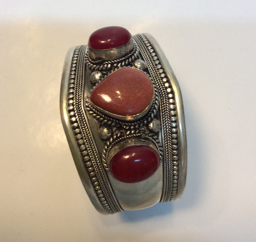 Cuff bracelet in silver metal with gold stone in the center, and 2 red agate on the sides at Bijou's Boutique.