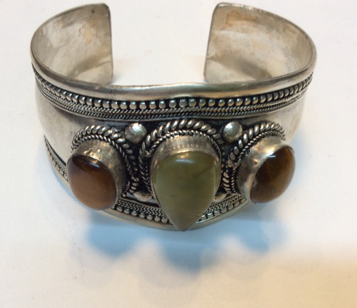 Cuff bracelet in silver metal, with flower jade in the center and 2 tiger eye stones on each side at Bijou's Boutique.