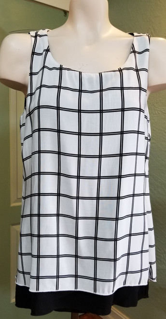 Michael Tyler Sleeveless Tunic at Bijou's Boutique.  Double layer White and Black print.  Solid black under   layer.  Small high low front hemline with black showing.  Split back detail.  100% Polyester.  Made in Canada.