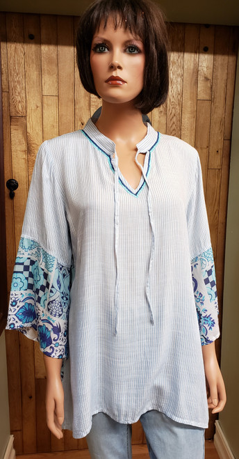 A & A Pinstripe and Floral Tunic at Bijou's Boutique. White with blue pinstripe front. Blue floral   back. V-neck mandarin collar with long ties. 100% Viscose.