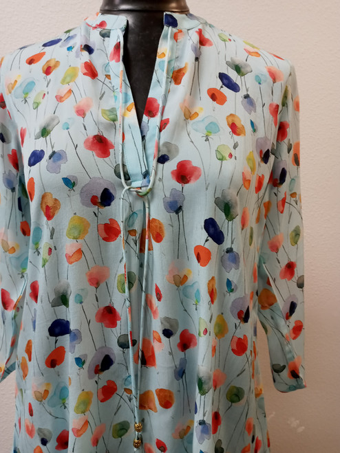 APNY Light Blue Floral Tunic at Bijou's Boutique. Beautiful floating flower pattern .V-neck with tie front.  Rounded hemline - higher on sides. Three-quarter sleeve length. 64% Cupro/36% Viscose.