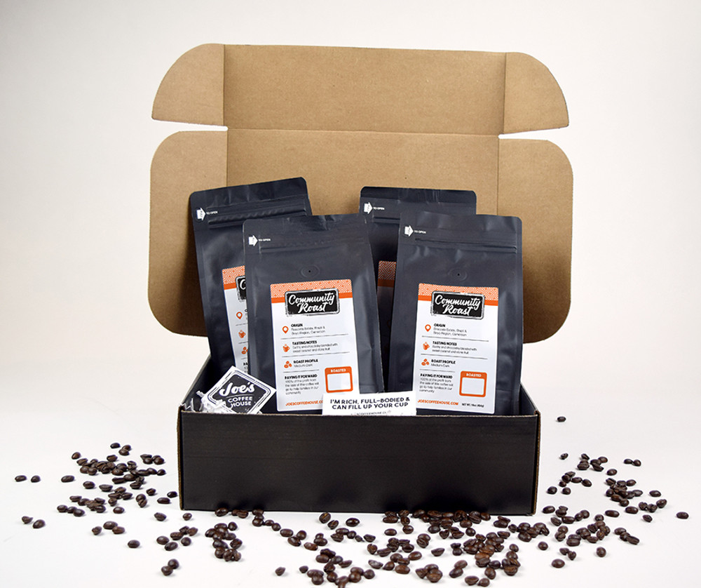 Four 16oz  Community Roast Coffee, A few of Joe's exclusive stickers all packed in a black box.