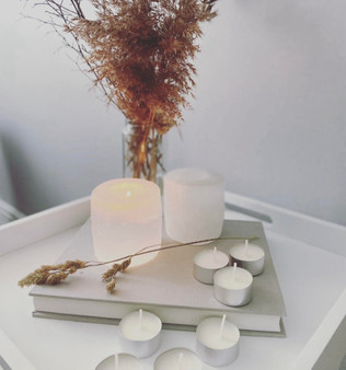 A white selenite crystal tea light holder is lit in the center of the image, with tea lights scattered around. In the background is a vase filled with dried pampas grass.
