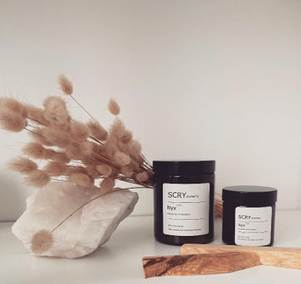 Two Nyx candles sit next to a large white crystal. A spring of dried flowers are in the background.