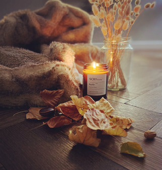 A lit candle in the scent North is on top of a wooden surface. Behind it in the background is a brown fur blanket, and some dried pampas grass. In the foreground is some dried autumn leaves.